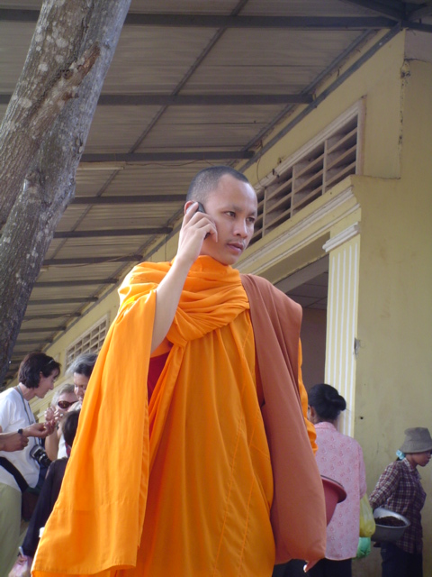 2006 Cambodia fried spider roadside market Buddhist monk on cell phone 02.jpg